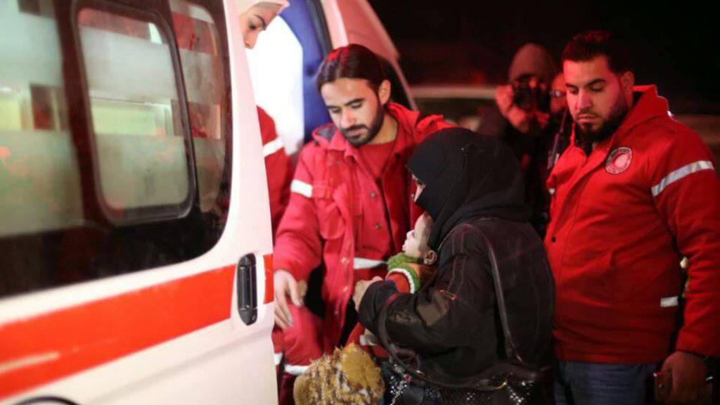 Helfer des syrischen Roten Halbmondes beim Transport Kranker in Ost-Ghuta