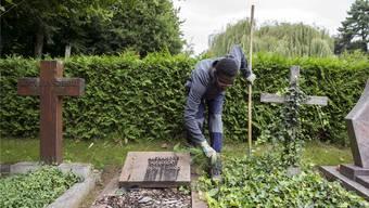 Ein Asylsuchender bei einem Arbeitseinsatz auf einem Friedhof bei Lausanne im Kanton Waadt.