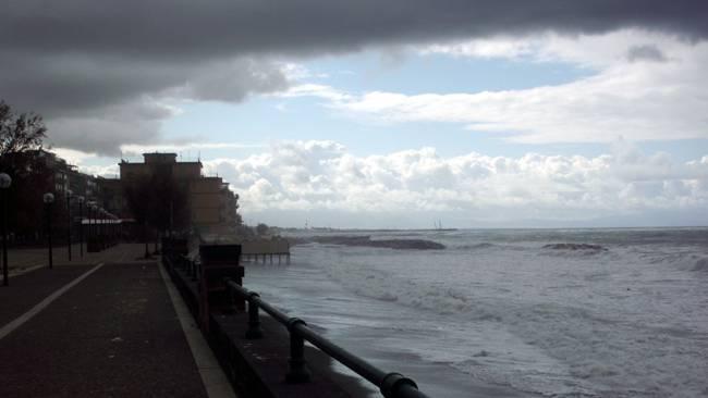 Der Wind treibt Wellen, Gischt und Wolken gegen die Küste.