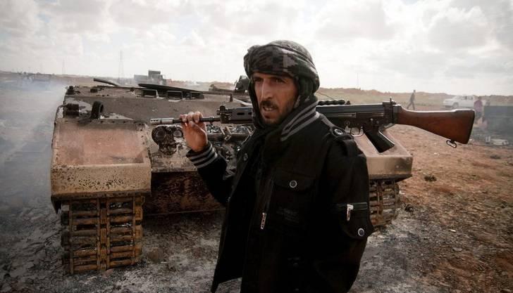 Ein Aufständischer neben einem von französischen Luftangriffen getroffenen Panzer von Gaddafi.