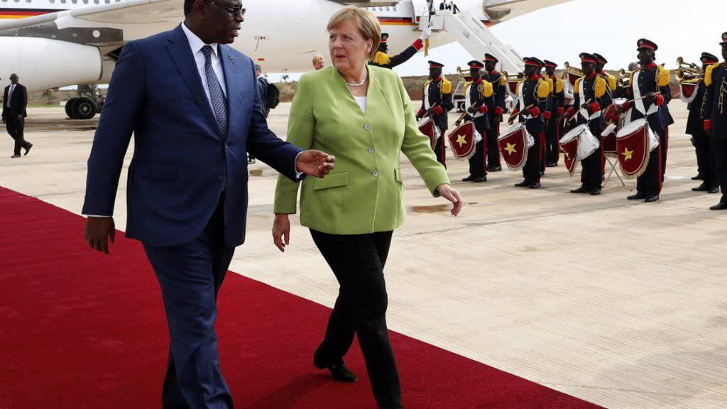 Die deutsche Kanzlerin Angela Merkel (rechts) hier zusammen mit Senegals Präsident  Macky Sall (links) wurde bei ihrem Staatsbesuch in Senegal mit militärischen Ehren und deutschen Schlagern empfangen.