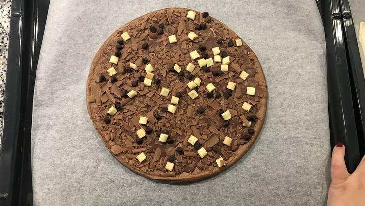 So sieht sie ausgepackt und noch gefroren aus. Ein dunkler und süsser Pizzateig mit Schokoladenbelag und -Stückchen.