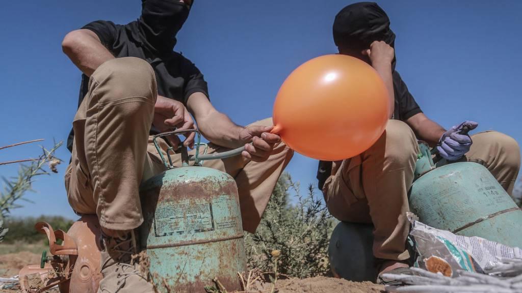 Maskierte Palästinenser füllen in einem Gebiet östlich von Gaza-Stadt Ballons mit Kühlgas, die dann mit Brandsätzen und brennbarem Material versehen werden und vom Wind in israelisches Gebiet getragen werden sollen. Foto: Mohammed Talatene/dpa Foto: Mohammed Talatene/dpa
