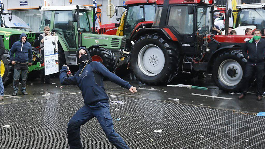 Bauern protestieren in Brüssel gegen den Preiszerfall: Ein Mann schleudert eine Flasche in Richtung der Polizisten.