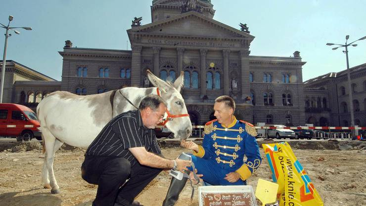 Der Politiker Alexander Tschäppät, links, schenkt dem Komiker Massimo Rocchi und seinem Zirkus-Esel Silva ein paar Knieschoner. 2003