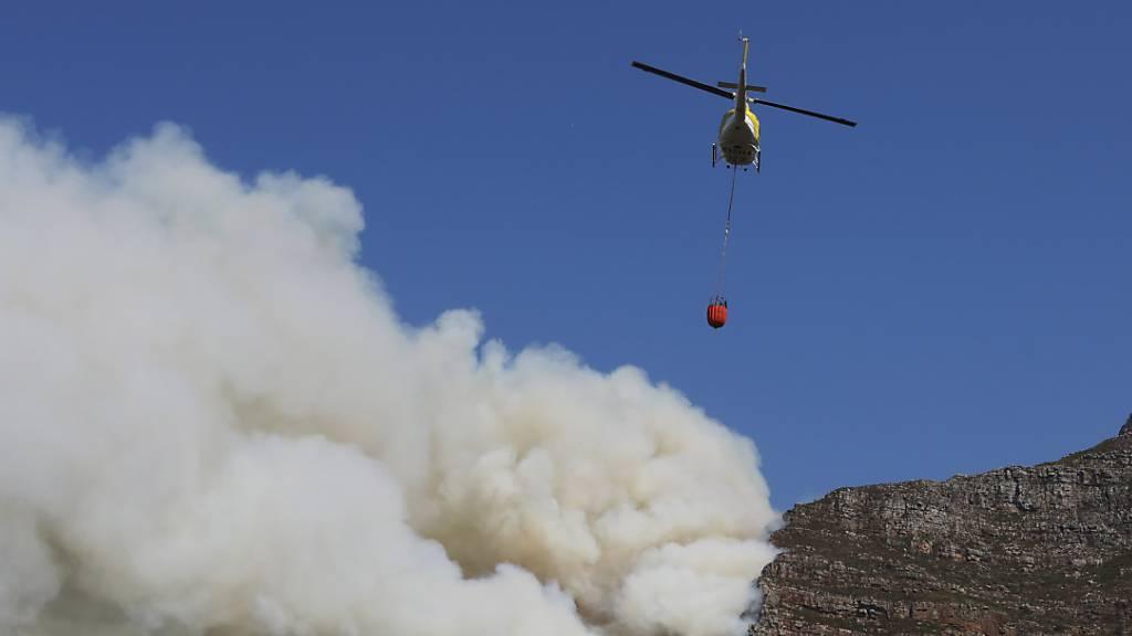 Ein Helikopter wirft Wasser über einem Brand auf dem Tafelberg ab. Foto: Nardus Engelbrecht/AP/dpa
