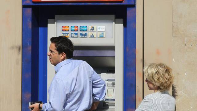 Ein Mann hebt von einem Geldautomaten in Athen Geld ab (Archiv)