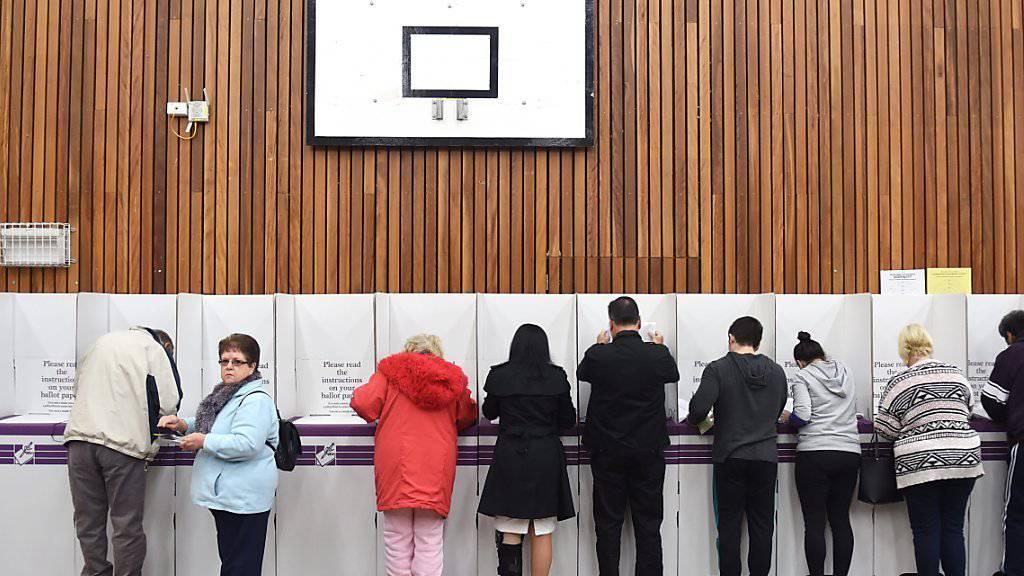 Australier geben in einer Turnhalle ihre Stimme ab. Jetzt sind die meisten Wahllokale geschlossen und die Stimmauszählung beginnt.