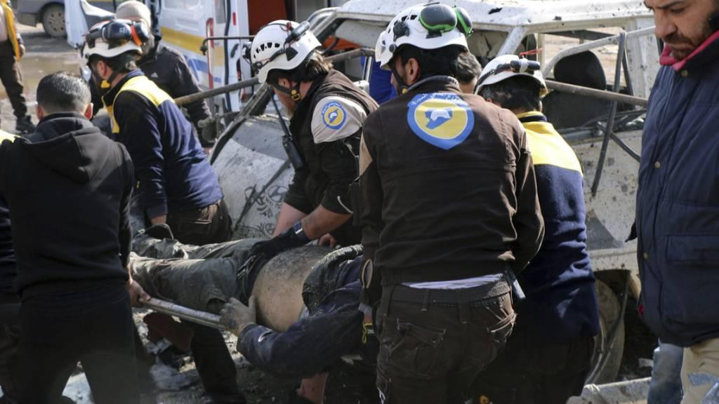 Helfer der Rettungsorganisation Weisshelme transportieren einen verletzten Zivilisten in Marat al-Numan (Provinz Idlib). Syrische und russische Jets hatten den Markt der Stadt bombardiert.