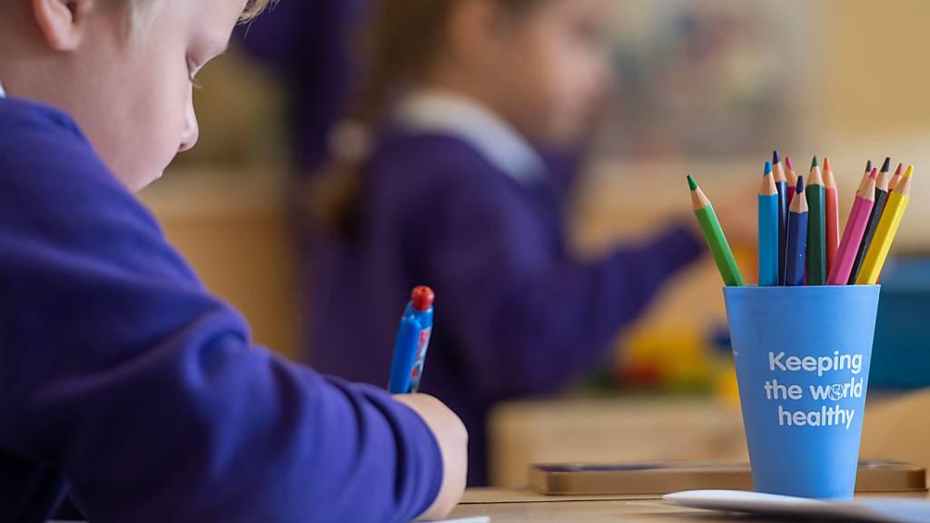 Ein Schüler sitzt an einem Tisch in einem Klassenzimmer der Grundschule «Queen's Hill Primary School», vor ihm steht ein Stiftebecher mit der Aufschrift «Keeping the world healthy».