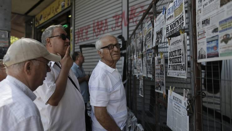 Griechen betrachten die Zeitungsaushänge in Athen.