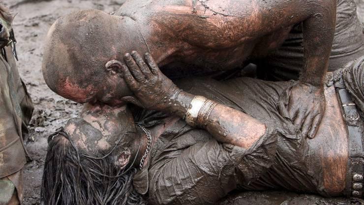 Zwei schlamverschmierte Festivalbesucher küssen sich