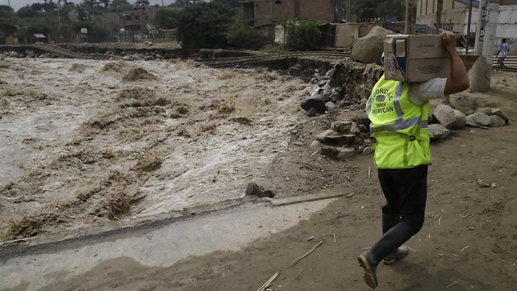 Helfer versorgen Menschen, die in der Nähe Limas durch Überschwemmungen und Erdrutsche isoliert wurden. Eine rätselhafte Meerwassererwärmung vor der peruanischen Küste hat die Katastrophen ausgelöst.