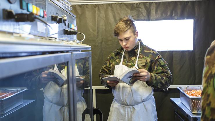 Die Küchenchef Unteroffiziersschule aus Thun kocht für die Gemeinde Luterbach. Noch schnell das Kochbuch konsultieren