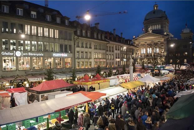 """Besucher strömen in den frühen Morgenstunden durch die Strassen von Bern, im Hintergrund das Bundeshaus, während dem traditionellen """"Zibelemärit"""""""