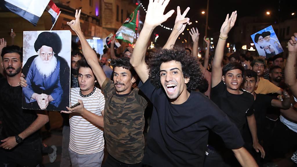 Anhänger des schiitischen Klerikers Al-Sadr feiern mit seinen Plakaten nach der Bekanntgabe der Ergebnisse der Parlamentswahlen auf dem Tahrir-Platz in Bagdad, Irak. Foto: Hadi Mizban/AP/dpa