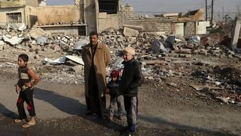 Eine Familie steht vor ihrem zerstörten Haus im Ostteil von Mossul.