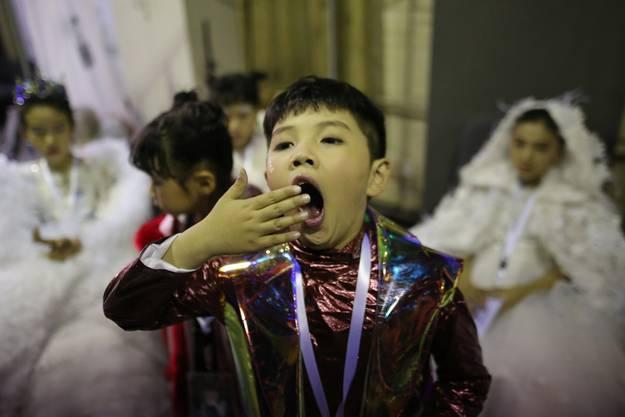 Ein Junge gähnt hinter den Kulissen an der China Fashion Week in Peking, 26. März 2018.