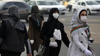 Gesichtsmasken in Teheran: Die Menschen wappnen sich gegen das Virus, die Regierung spielt die Zahl der Infizierten wohl herunter. (AP Photo/Vahid Salemi)