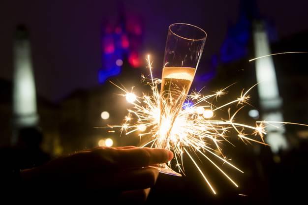Une personne pose avec une coupe de champagne et un feu de Bengale lors du passage de la nouvelle annee 2017 devant l'illumination de la Cathedrale de Lausanne durant la nuit du samedi 31 decembre 2016 au dimanche 1 janvier 2017 a Lausanne. (KEYSTONE/Jean-Christophe Bott)