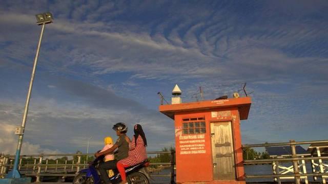 Familie in Aceh vor einer Tsunami-Warnungs-Anlage (Symbolbild)