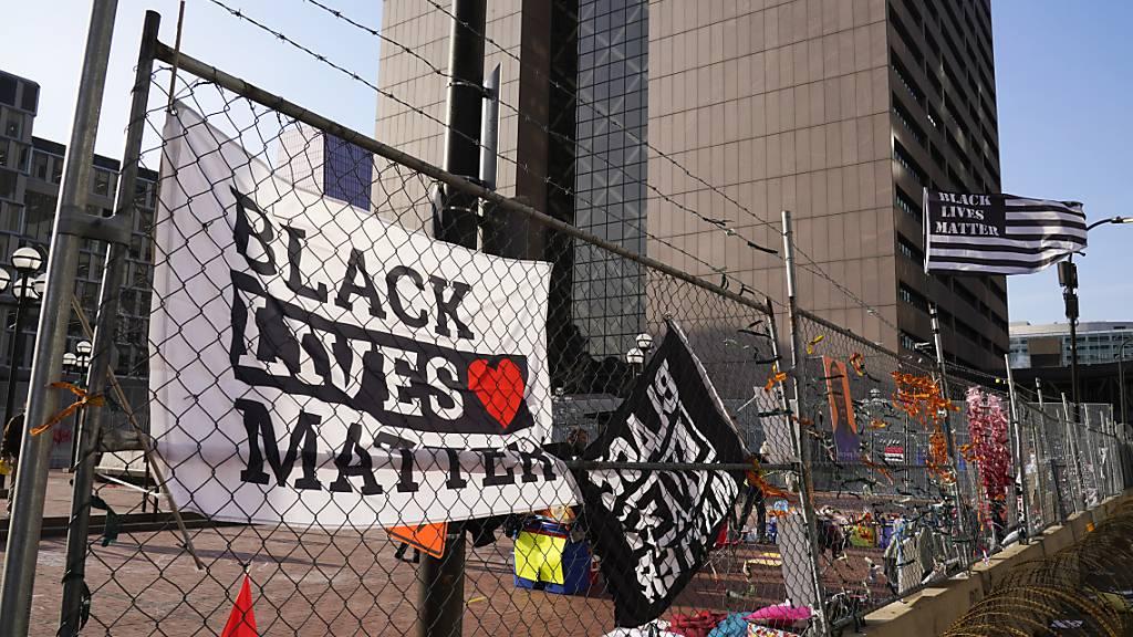 Fahnen und Plakate hängen am Zaun vor dem Regierungszentrum von Hennepin County, in dem der Prozess gegen den ehemaligen Polizisten Chauvin stattfindet. Foto: Jim Mone/AP/dpa