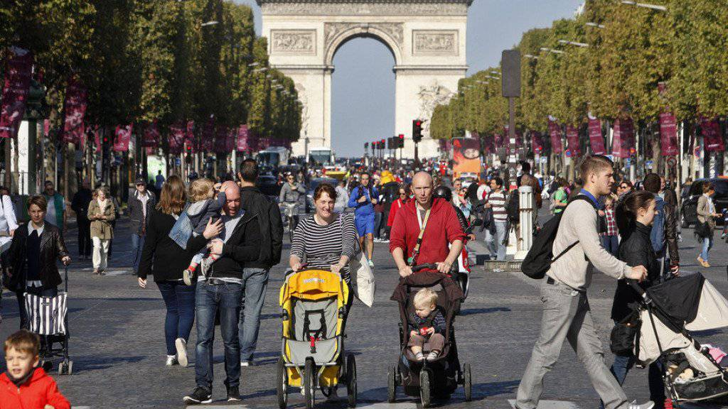 Leute flanieren auf den Champs-Élysées. Wie im vergangenen Jahr waren in Paris wieder grosse Teile der Stadt für den motorisierten Verkehr gesperrt. (Archiv)
