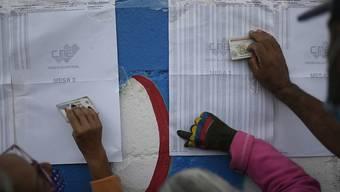 Einwohner von Caracas überprüfen auf einem Aushang, in welchem Wahllokal sie ihre Stimme abgeben müssen. Foto: Matias Delacroix/AP/dpa