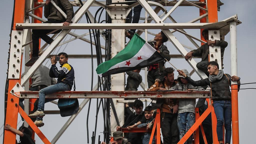 Ein Mann schwenkt in Idlib eine Fahne der syrischen Opposition während einer Massendemonstration zum zehnten Jahrestag des Beginns des syrischen Bürgerkriegs. Foto: Anas Alkharboutli/dpa