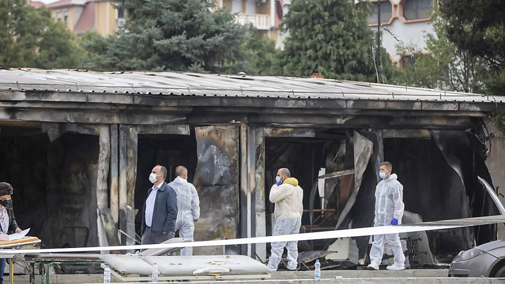 Gerichtsmediziner arbeiten nach einem Brand in einem Behelfskrankenhaus. Nach Angaben des Gesundheitsministeriums in Skopje sind bei dem Brand in Nordmazedonien in der Nacht zum Donnerstag 14 Patienten ums Leben gekommen. Foto: Visar Kryeziu/AP/dpa