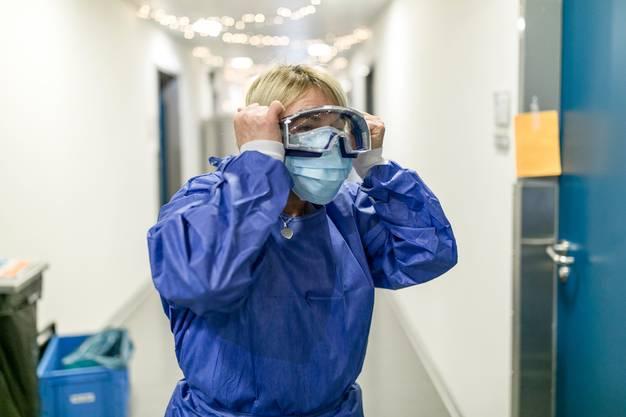 Reinigungsfachfrau Shukrije Sahiti trägt Schutzmantel, FFP2-Maske, Hygienemaske und Schutzbrille. Jetzt fehlen nur noch die Handschuhe.