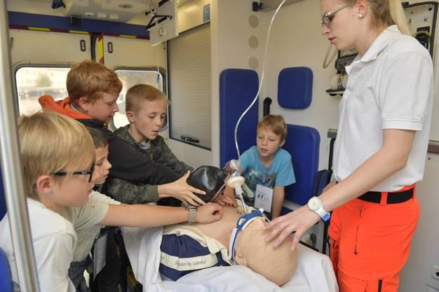 Michèle Kohler vom Rettungsdienst Grenchen erklärt den Kindern im Rettungsfahrzeug an einer Puppe verschiedene Dinge, wie Infusion stecken oder Beatmen.