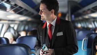 Ein Zugbegleiter kontrolliert die Billette und gibt Auskünfte zun Bahnbetrieb. (KEYSTONE/Christian Beutler)