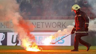 A firefighter removes light flares launching by Grasshopper's supporters, during the Super League soccer match of Swiss Championship between FC Sion and Grasshoppers Club, at the Stade de Tourbillon stadium, in Sion, Switzerland, Saturday, March 16, 2019. (KEYSTONE/Salvatore Di Nolfi)
