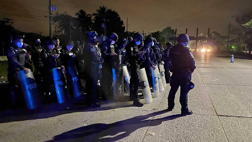 Polizisten stehen bereit, um den Weg einer Gruppe von Migranten zu blockieren, die auf ihren Weg in die USA die Grenze zu Guatemala überqueren zu versuchen. Foto: Moises Castillo/AP/dpa