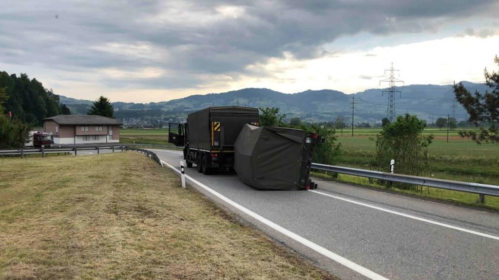 Lieferwagenlenker drängt Armeelaster ab - Anhänger kippt um