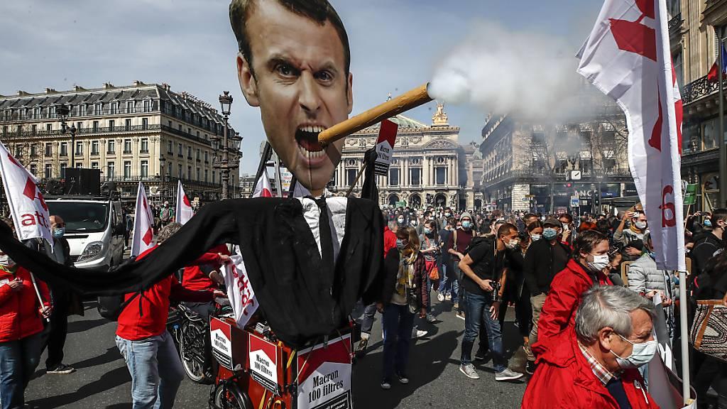 dpatopbilder - Demonstranten nehmen in Paris mit einem Plakat, das den französischen Präsidenten Macron mit einer rauchenden Zigarre darstellt, an einer Kundgebung für eine beherztere Klimapolitik teil. Foto: Michel Euler/AP/dpa