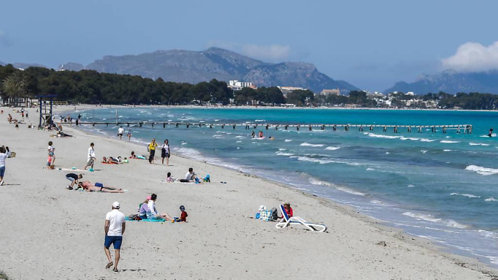 ARCHIV - Menschen verbringen ihre Freizeit am Strand von Mallorca. Foto: Clara Margais/dpa