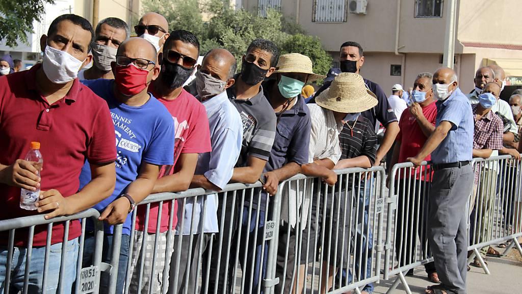 Einwohner des Ortes Oued Ellil warten vor einer Schule, um sich während einer Impfaktion mit dem Corona-Impfstoff Vaxzevria impfen zu lassen. In Tunesien sind laut Angaben des Gesundheitsministeriums bei einer landesweiten Impfaktion gut 550 000 Menschen gegen das Coronavirus immunisiert worden. Foto: Hassene Dridi/AP/dpa