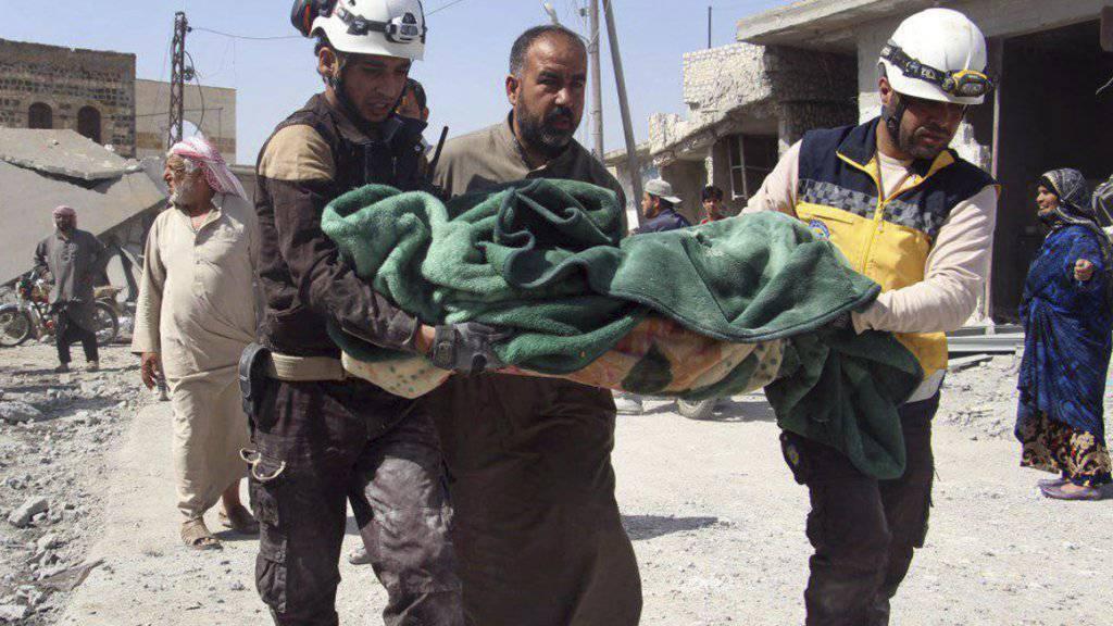 Freiwillige der Helferorganisation Weisshelme bergen ein Opfer nach Luftangriffen auf einen Markt im Dorf Ras al-Ain in der Provinz idlib. (Bild vom 7. Mai).