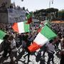 Teilnehmer einer Demonstration gegen die staatliche Corona-Politik schwenken italienische Nationalflaggen. Foto: Gregorio Borgia/AP/dpa