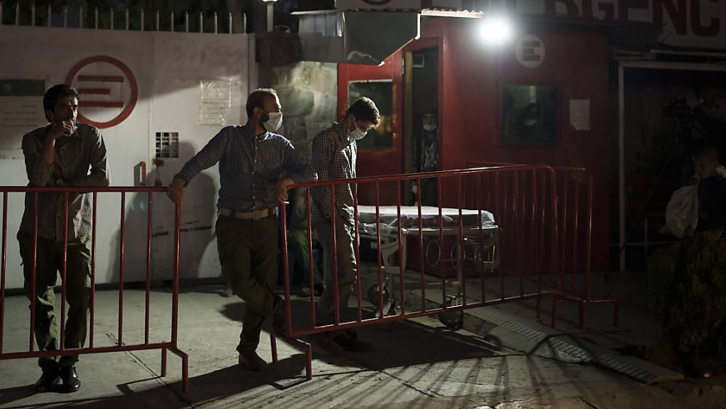 Arbeiter warten nach einer Explosion an der Eidgah-Moschee vor dem Emergency NGO Krankenhaus.