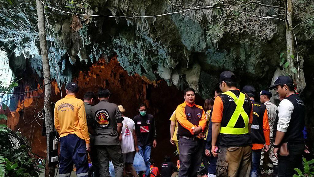 Retter und Parkverantwortliche am Eingang der Höhle in Thailand, in der die Junioren-Mannschaft und ihr Trainer festsitzen.
