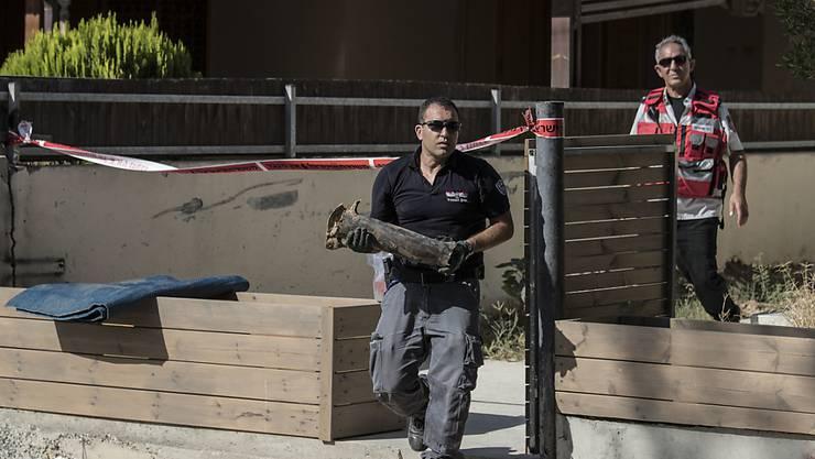 Ein israelischer Polizist trägt ein Raketenteil aus einem Hof in der Stadt Sderot.