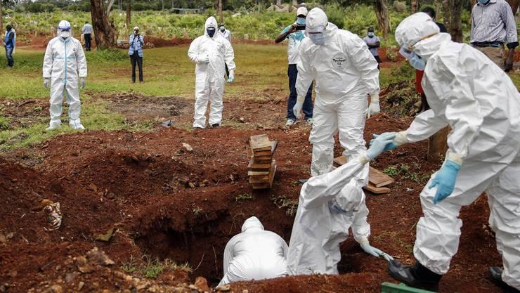 Bestattungsbeamte in Schutzkleidung beerdigen ein Coronavirus-Todesopfer auf dem Langata-Friedhof in Nairobi, der Hauptstadt Kenias. (Symbolbild.)