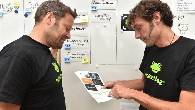 Zwei der drei Gründer von Ticketfrog schauen sich ein ausgedrucktes Ticket mit sechs Werbeplätzen an: Reto Baumgartner (links) und Mike Müller.