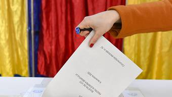 Eine Frau gibt ihren Stimmzettel ab. Foto: Andreea Alexandru/AP/dpa