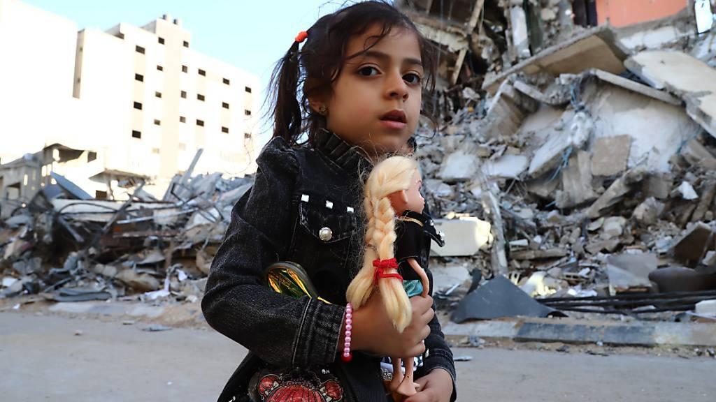 dpatopbilder - Ein Mädchen geht vorbei an von Luftangriffen zerstörten Häusern. Seit dem 10. Mai beschießen militante Palästinenser Israel mit Raketen. Israels Armee reagiert darauf mit Angriffen auf Ziele im Gazastreifen, vor allem durch die Luftwaffe. Auf beiden Seiten gab es Tote. Foto: Naaman Omar/APA Images via ZUMA Wire/dpa