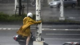 Eine Rollerfahrerin im Süden Taiwans hält sich wegen der starken Winde an einem Strassenpfosten fest.