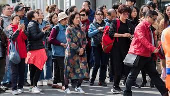 Asiatische Touristen auf dem Schwanenplatz in der Stadt Luzern.